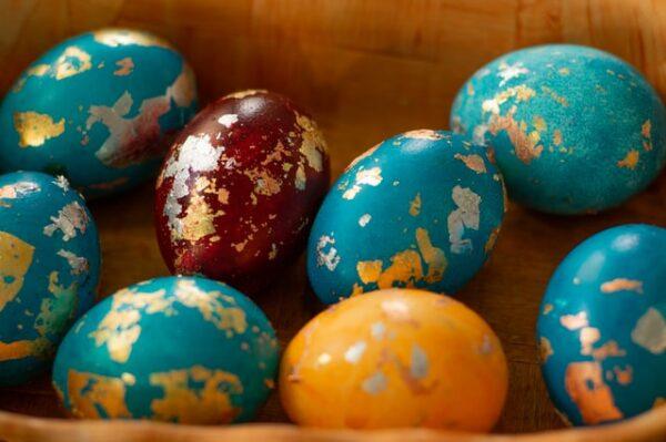 Bunte Eier, welche mit Gold verziert wurden, liegen beieinander