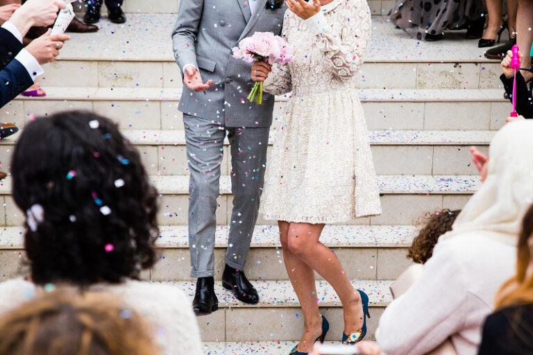 Ein Hochzeitspaar steht auf einer Treppe, die Gäste streuen Glitter