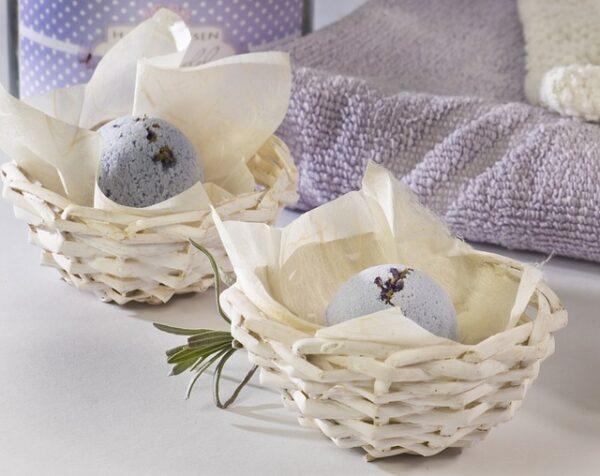 Lilane Badebomben mit Lavendelblüten liegen in kleinen Körben