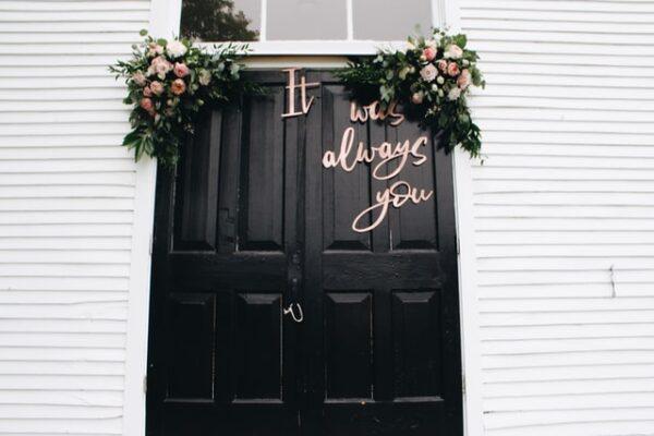 Eine Tür wurde mit Blumen und einem Spruch für eine Hochzeit dekoriert