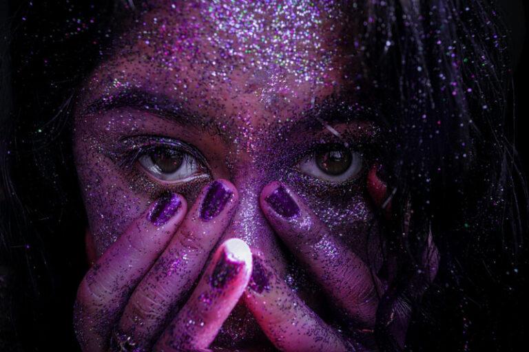 Eine Nahaufnahme einer Frau, die violett angeleuchtet wird und Glitzer im Gesicht hat