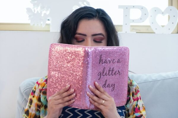 Eine Frau liest ein Buch in einem pink glitzernden Umschlag
