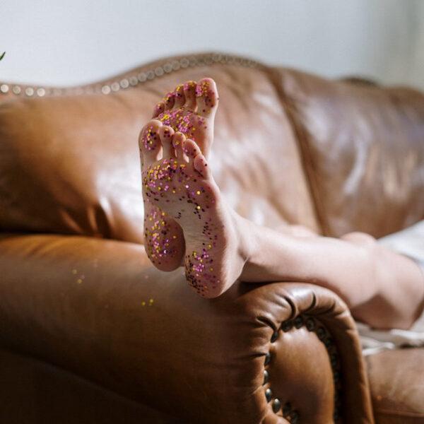Jemand liegt auf der Couch und an den Füßen klebt bunter Glitzer