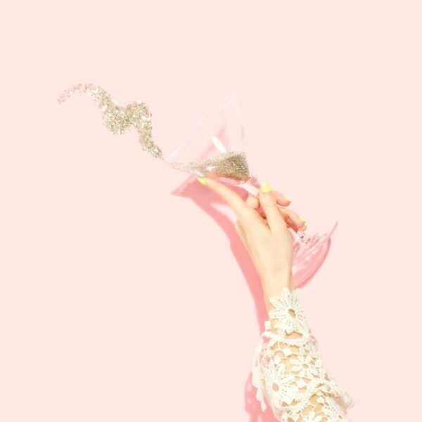 Eine Person hält ein Martiniglas in der Hand, welches mit Glitzer gefüllt ist, und winkt mit Schwung