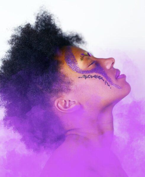 Eine Frau wurde mit violettem Glitzer im Gesicht geschminkt. Unter ihr steigt lilaner Nebel auf