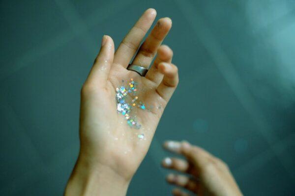 Auf einer Hand liegen einige Glitzerpartikel in Sternform