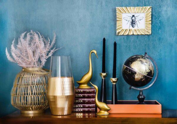 Auf einer Holzoberfläche stehen verschiedene Dekoelemente, darunter eine Vase, die zur Hälfte mit einer goldenen Farbe verziert wurde