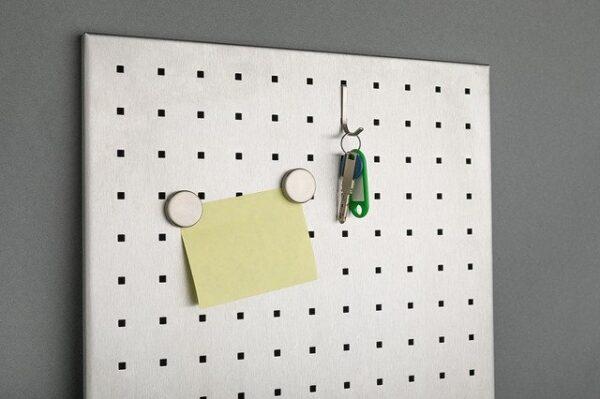 An einem Metallbrett wurden mit Magneten ein Zettel und ein Schlüsselbund befestigt