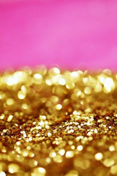 Vor einem pinken Hintergrund sieht man gold glänzende Glitzerpartikel