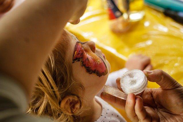 Einem Kind wird mit Glitzer und Farbe ein Schmetterling auf das Gesicht gemalt