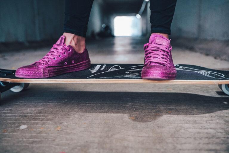 Eine Person steht auf einem Longboard. während sie pinke Glitzer-Schuhe trägt