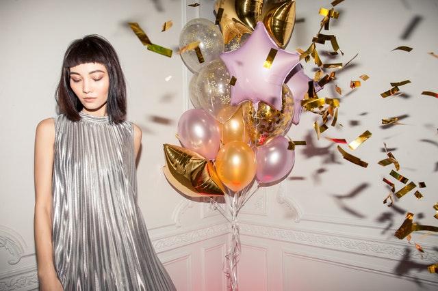 Eine Frau in einem silbernen Kleid steht neben Luftballons und goldenem Konfetti